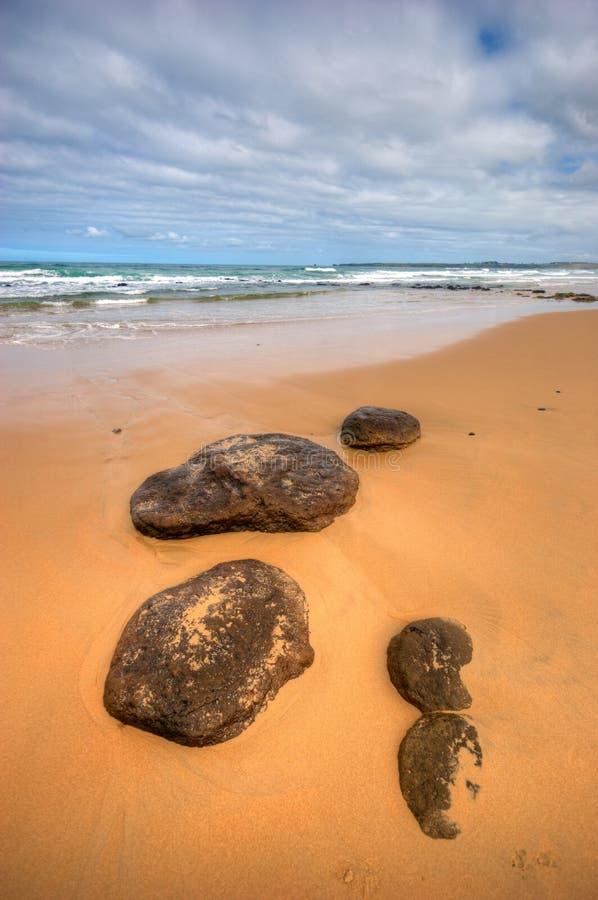 Opinião de baixo ângulo das rochas na praia no console de Phillip imagens de stock
