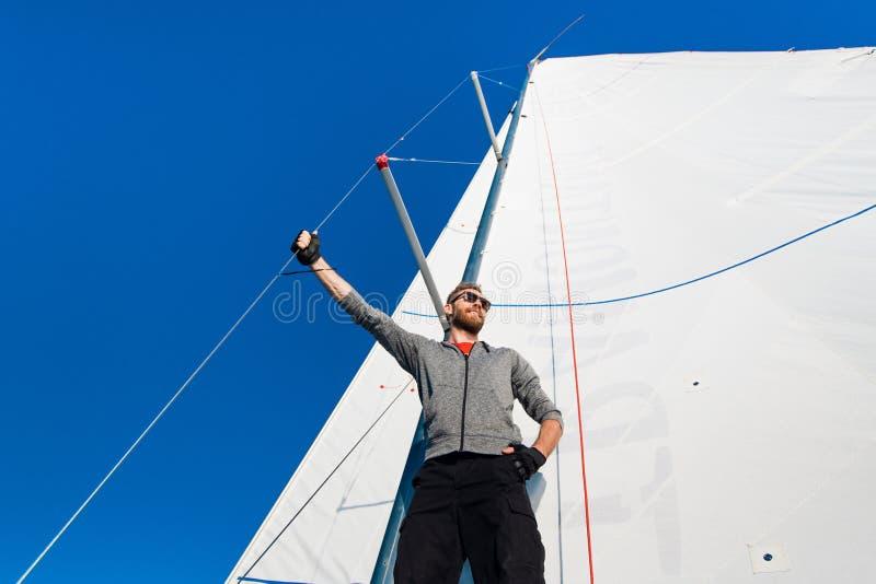Opinião de baixo ângulo do sarilho de funcionamento do marinheiro no iate Trabalho com cordas e vela imagem de stock royalty free