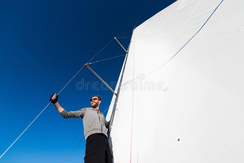 Opinião de baixo ângulo do sarilho de funcionamento do marinheiro no iate Trabalho com cordas e vela foto de stock