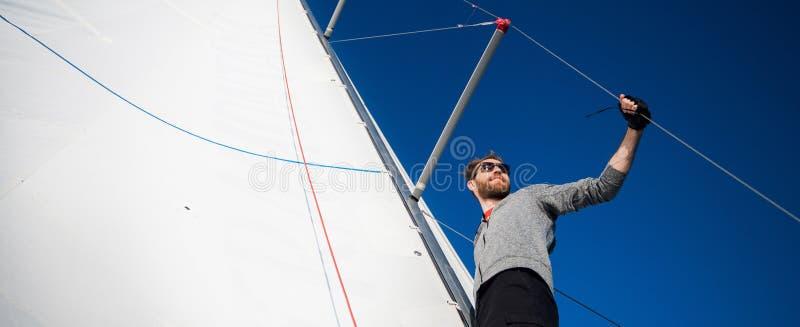 Opinião de baixo ângulo do sarilho de funcionamento do marinheiro no iate Trabalho com cordas e vela fotografia de stock royalty free