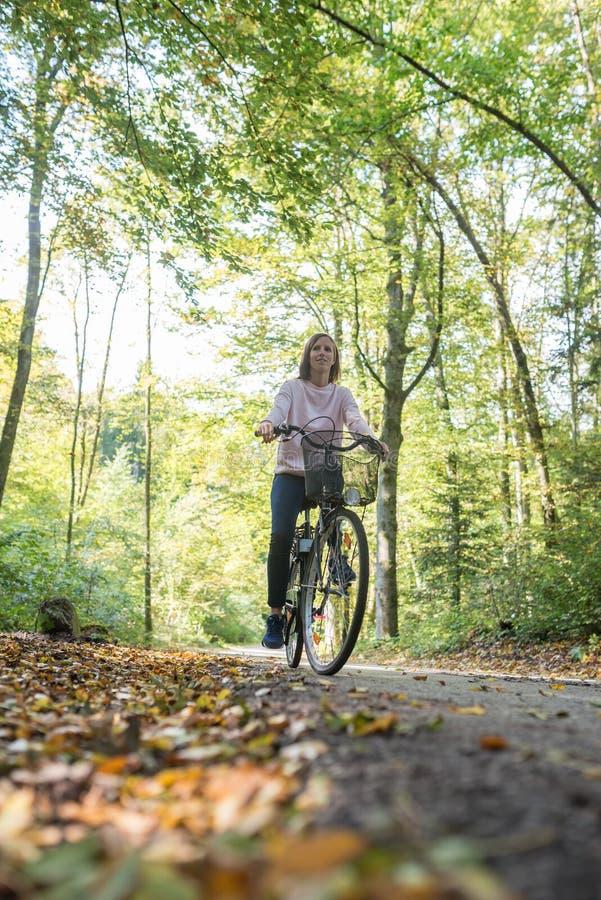Opinião de baixo ângulo a jovem mulher que monta uma bicicleta fotografia de stock royalty free
