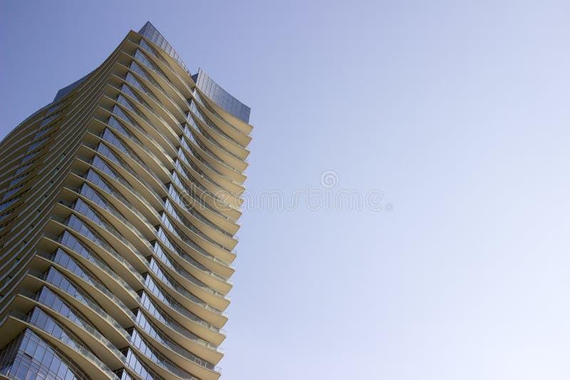 Opinião de baixo ângulo lateral de um prédio de escritórios incorporado moderno do arranha-céus com saliências amareladas em cada fotos de stock