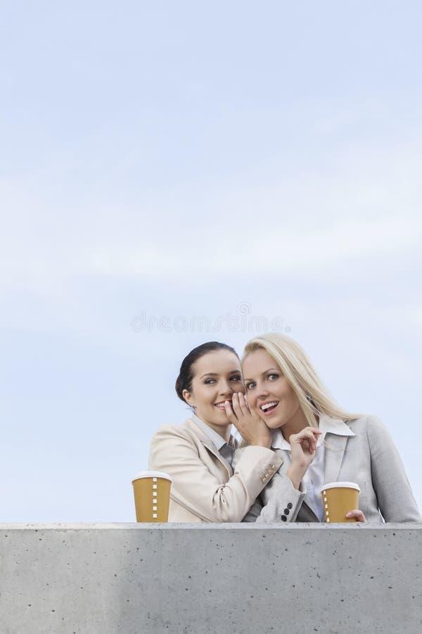 Opinião de baixo ângulo a mulher de negócios feliz que sussurra na orelha do colega de trabalho ao estar no terraço contra o céu fotos de stock royalty free
