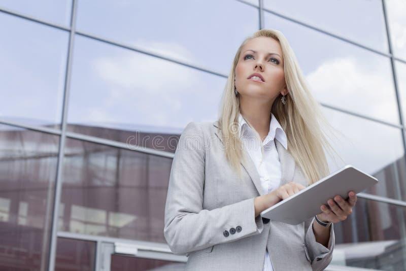 Opinião de baixo ângulo a mulher de negócios que guarda a tabuleta digital ao olhar afastado contra o prédio de escritórios fotografia de stock