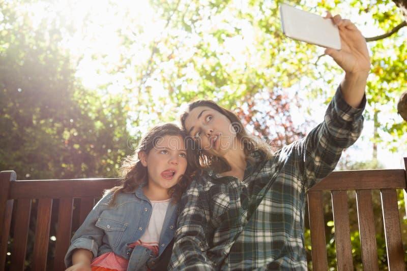 Opinião de baixo ângulo a mulher que toma o selfie com filha ao fazer as caras contra árvores fotos de stock