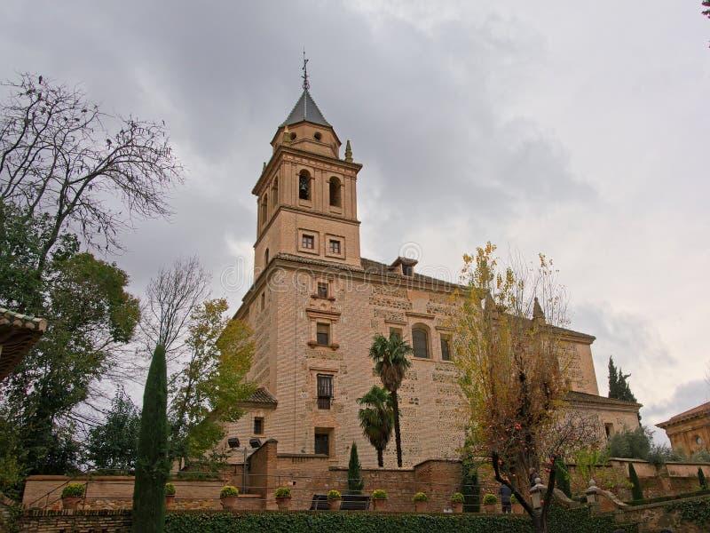 Opinião de baixo ângulo na igreja de Santa Maria de Alhambra, Granada, Espanha, cercada por árvores em um dia nebuloso fotografia de stock