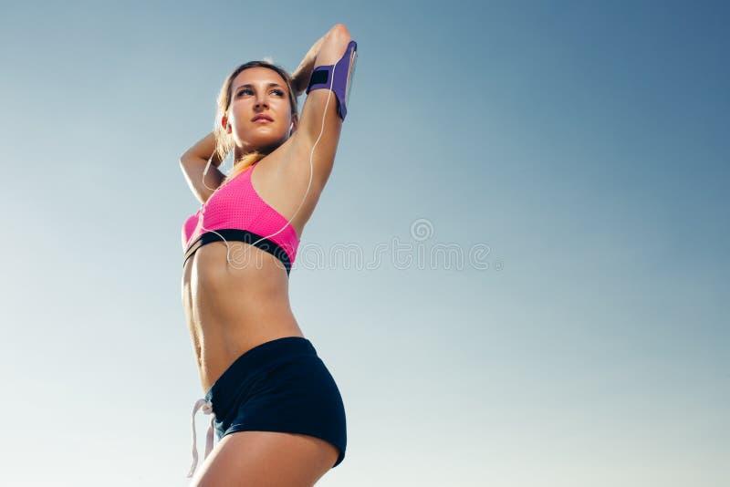 opinião de baixo ângulo o atleta fêmea nos fones de ouvido com o smartphone na caixa de corrida da fita que estica contra fotos de stock