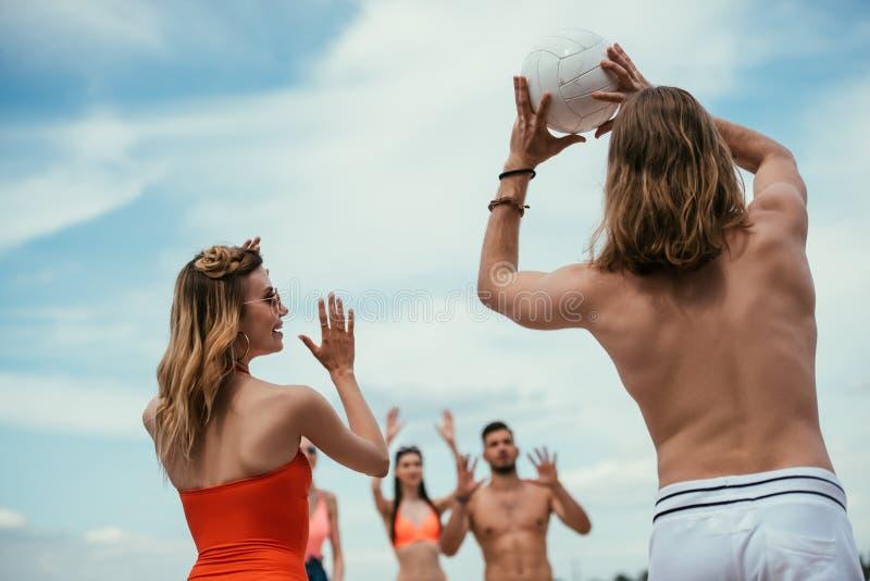 opinião de baixo ângulo o homem novo e os amigos fêmeas que jogam o voleibol fotos de stock