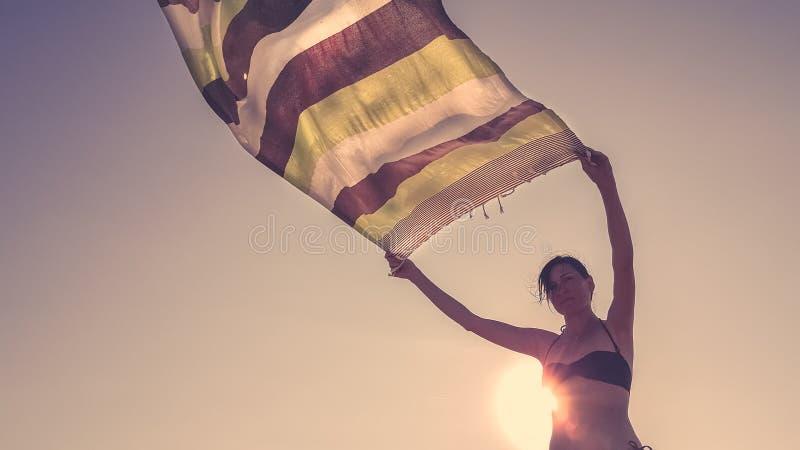 Opinião de baixo ângulo uma mulher caucasiano que guarda uma tela da tanga acima no ar para deixá-lo seco no vento imagens de stock royalty free