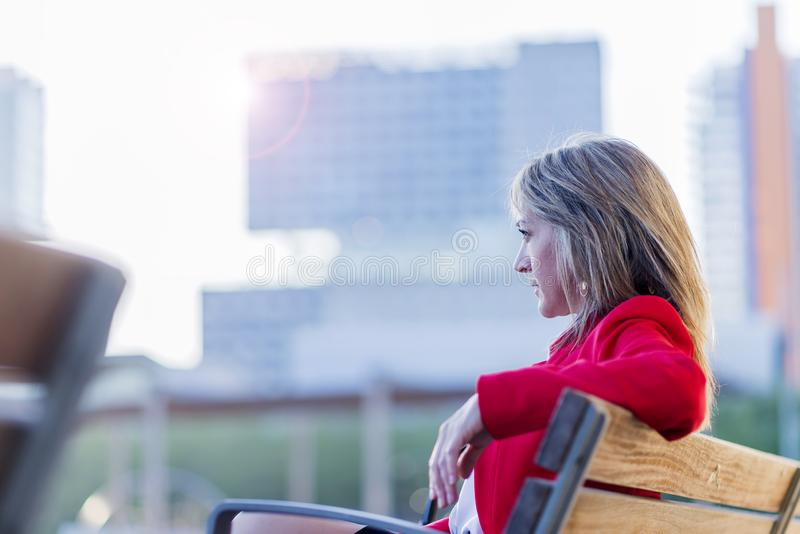 Opinião de baixo ângulo uma mulher loura elegante no revestimento vermelho que senta-se em um ar livre do banco ao olhar afastado fotografia de stock royalty free