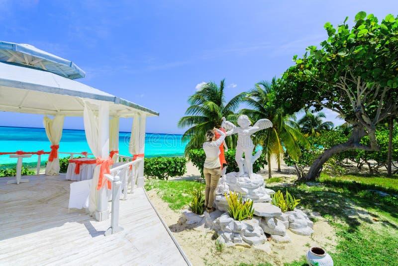 opinião de convite bonita uma moça, decoração da senhora, preparando o miradouro da praia para um oceano tranquilo da cerimônia d imagens de stock