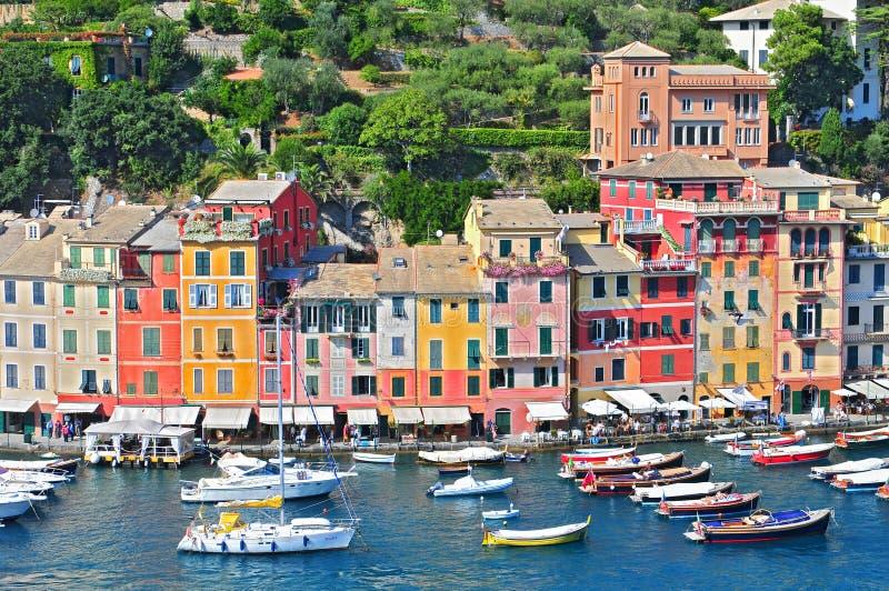 Opinião de Liguria Portofino do porto com barcos amarrados e as casas coloridas pasteis que alinham a baía com as árvores em mont fotografia de stock royalty free