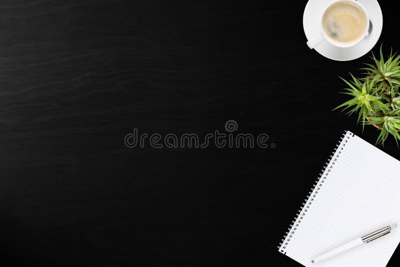 Opinião de madeira preta do desktop do escritório com bloco de notas, pena, planta e c fotos de stock