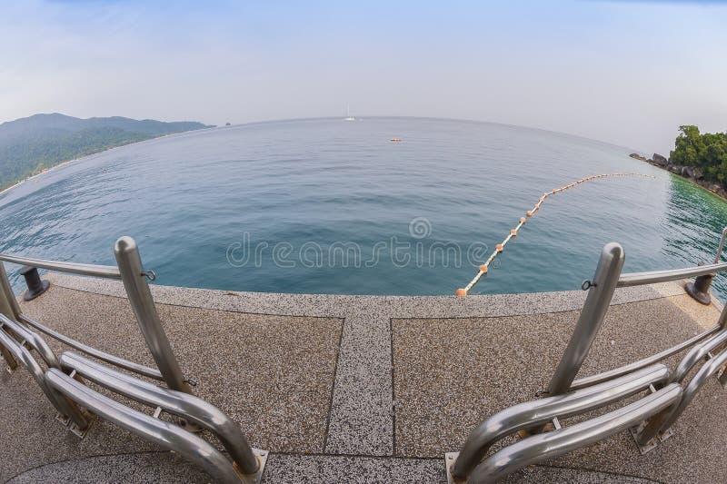 Opinião de olhos de peixes na praia e no oceano tropicais foto de stock
