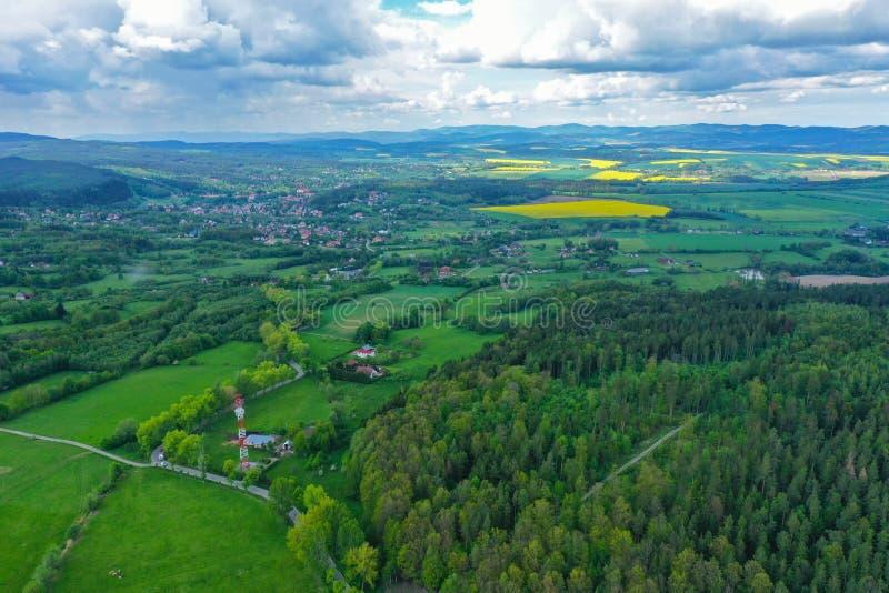 Opinião de perspectiva aérea em montanhas sudety com a cidade turística no vale cercado por prados, por floresta e por campos da  imagem de stock royalty free