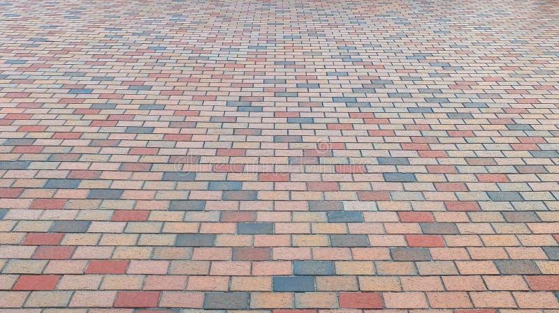 Opinião de perspectiva da estrada colorida da rua da pedra do tijolo Passeio, fundo da textura do pavimento imagem de stock