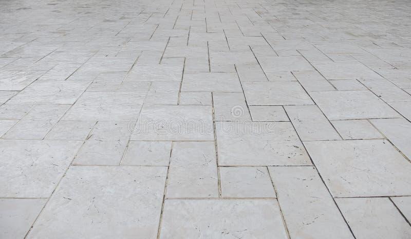 Opinião de perspectiva da pedra do tijolo do quadrado branco do Grunge na terra para a estrada da rua Passeio, entrada de automóv imagens de stock