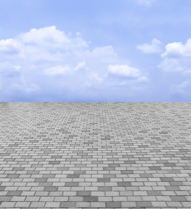 Opinião de perspectiva Gray Brick Stone Street Road monótonos Passeio, fundo da textura do pavimento com céu azul e nuvem fotografia de stock royalty free