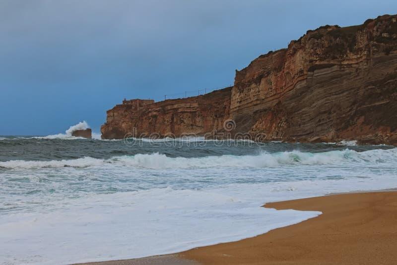 Opini?o de surpresa da paisagem de Oceano Atl?ntico tormentoso perto da cidade tur?stica famosa Nazare Rupturas grandes da onda s fotos de stock