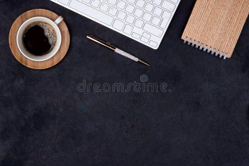 Opinião de tampo da mesa escura do escritório com copo e teclado de café fotografia de stock royalty free
