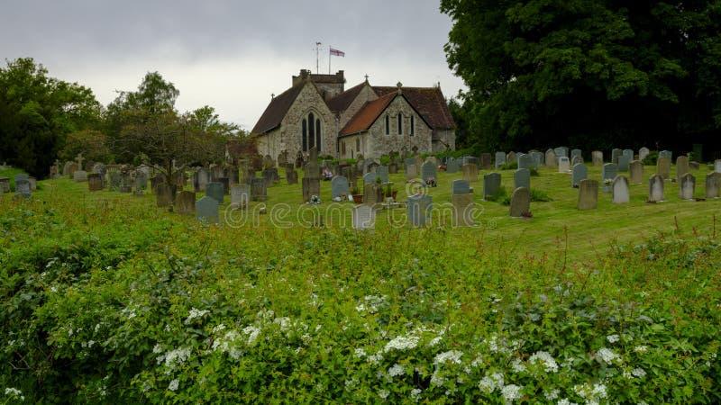 Opinião de tempo de mola em um dia nublado da porta norte que conduz do passeio de Lythes da igreja de St Mary, Selborne, Hampshi foto de stock
