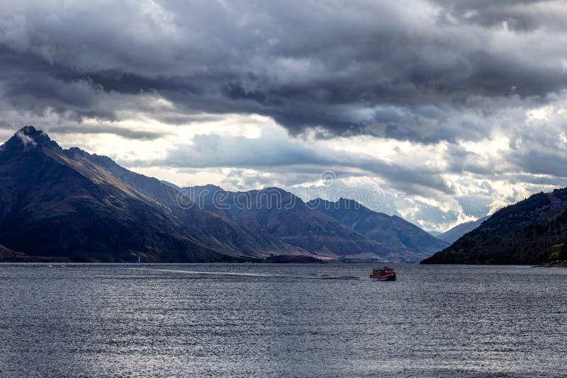 Opinião de Wakatipu do lago com um barco na noite com luz solar sobre as montanhas, Queenstown foto de stock