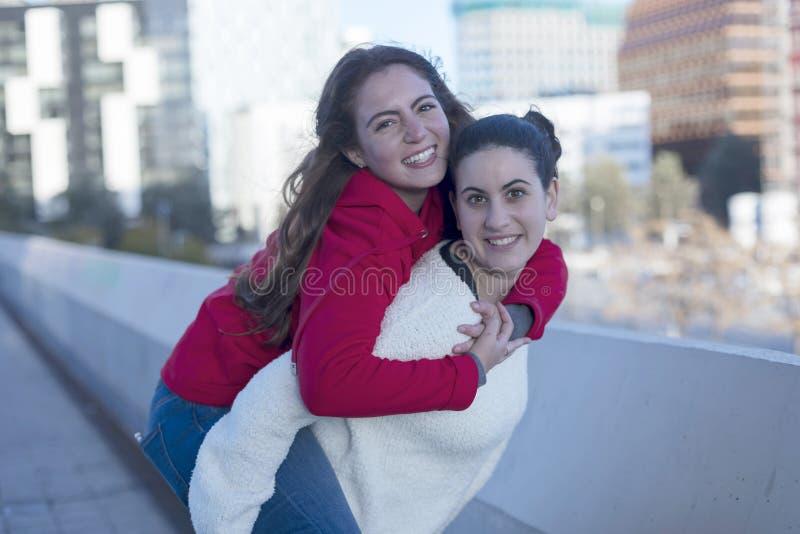 A opinião dianteira as melhores meninas de sorriso dos amigos reboca fora na cidade fotografia de stock royalty free