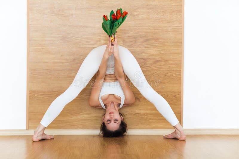 A opinião dianteira completo a jovem mulher desportiva em uma ioga praticando do terno branco que faz o straddle ereto dobra para foto de stock