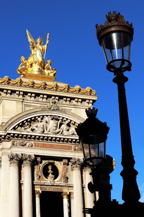 Opinião dianteira de Opera Paris Garnier da estátua dourada grande e da fachada na frente dos postes de luz velhos france foto de stock