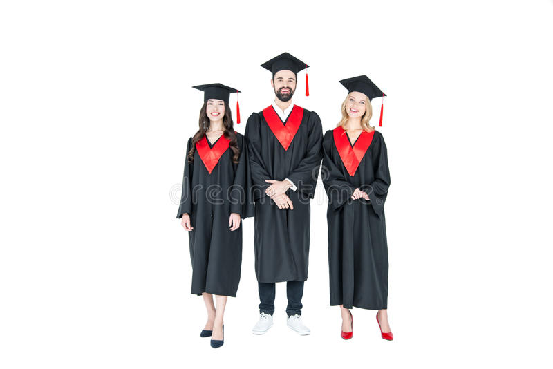 A opinião dianteira do comprimento completo estudantes felizes na graduação tampa a posição junto imagem de stock royalty free
