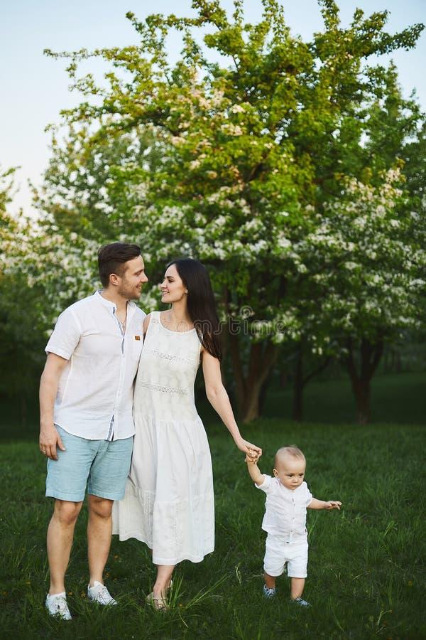 Opinião dianteira a família feliz nos equipamentos brancos que anda no parque imagens de stock