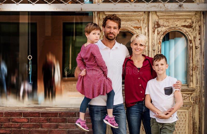 Opinião dianteira a família nova com as duas crianças pequenas que estão fora na cidade imagens de stock