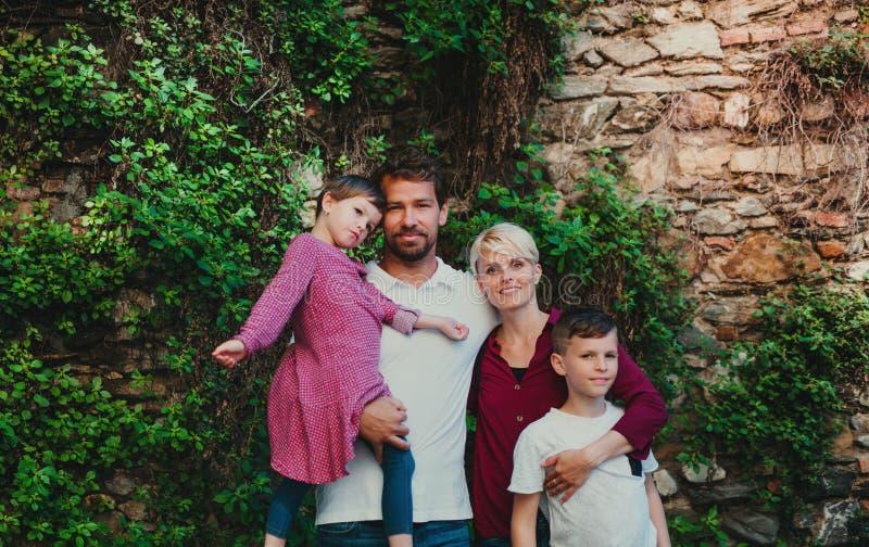 Opinião dianteira a família nova com as duas crianças pequenas que estão fora na cidade foto de stock royalty free