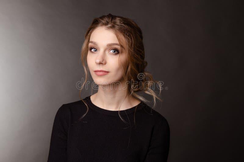 Opinião dianteira a menina agradável na roupa preta que whatcing a câmera e que levanta, retrato da mulher considerável foto de stock
