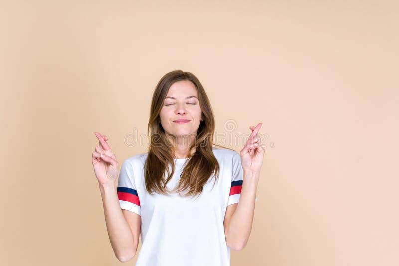 A opinião dianteira a mulher adulta nova com olhos fechados cruzou os dedos em duas mãos imagens de stock