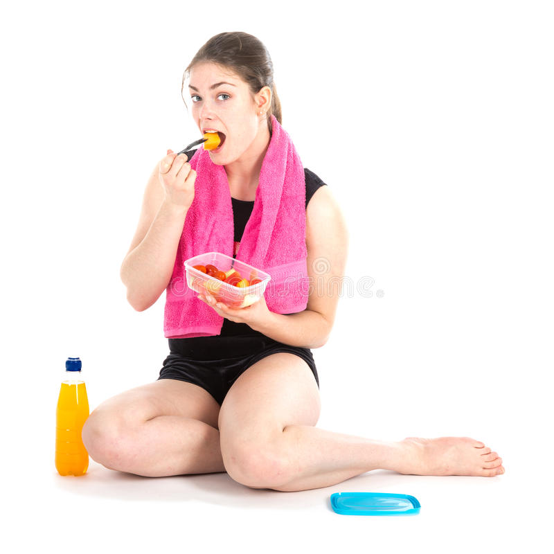 Opinião dianteira a mulher de assento com toalha roxa que come frutos frescos foto de stock