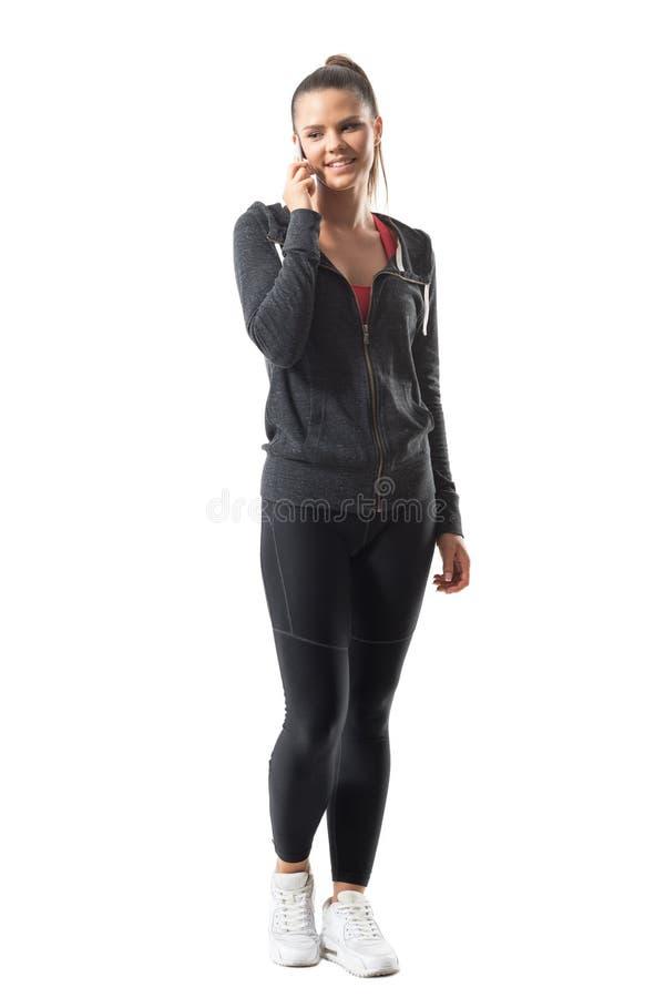 Opinião dianteira o desportista de sorriso feliz relaxado novo que fala no telefone que olha para baixo fotografia de stock