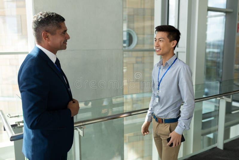 Opinião dianteira o homem de negócios caucasiano que discute com um homem de negócios asiático em uma passagem no escritório fotografia de stock