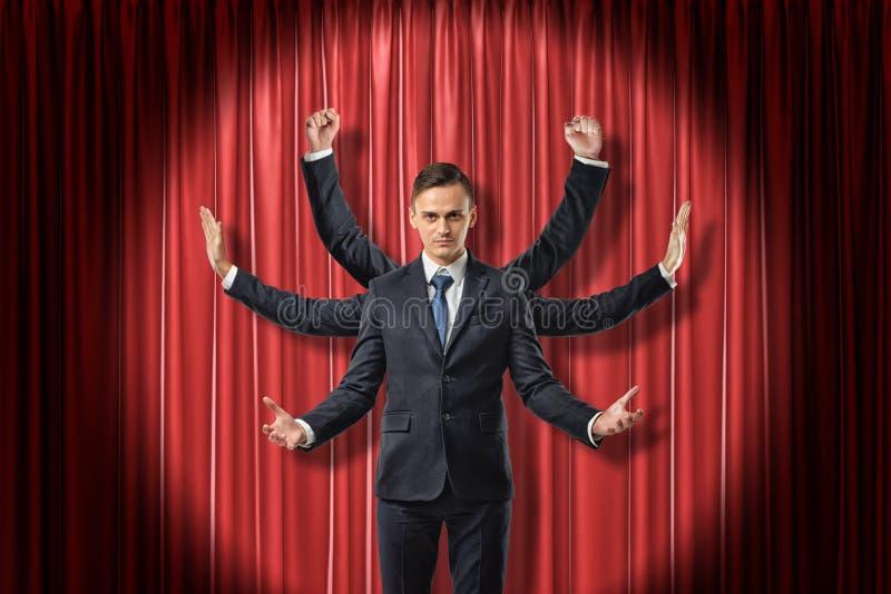 A opinião dianteira o homem de negócios multiarmed que levanta as mãos como Shiva, posição iluminou-se acima pelo projetor contra imagem de stock