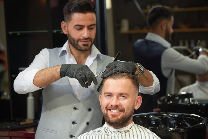 Opinião dianteira o homem de sorriso que obtém o penteado no barbeiro imagens de stock