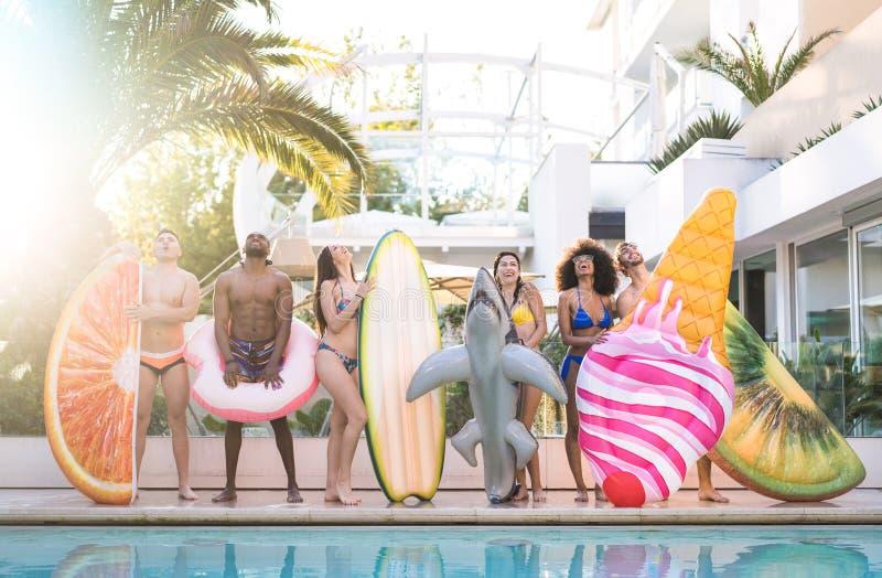 Opinião dianteira os amigos no partido de piscina com colchão de ar do lilo e no desgaste da nadada - conceito das férias da juve foto de stock