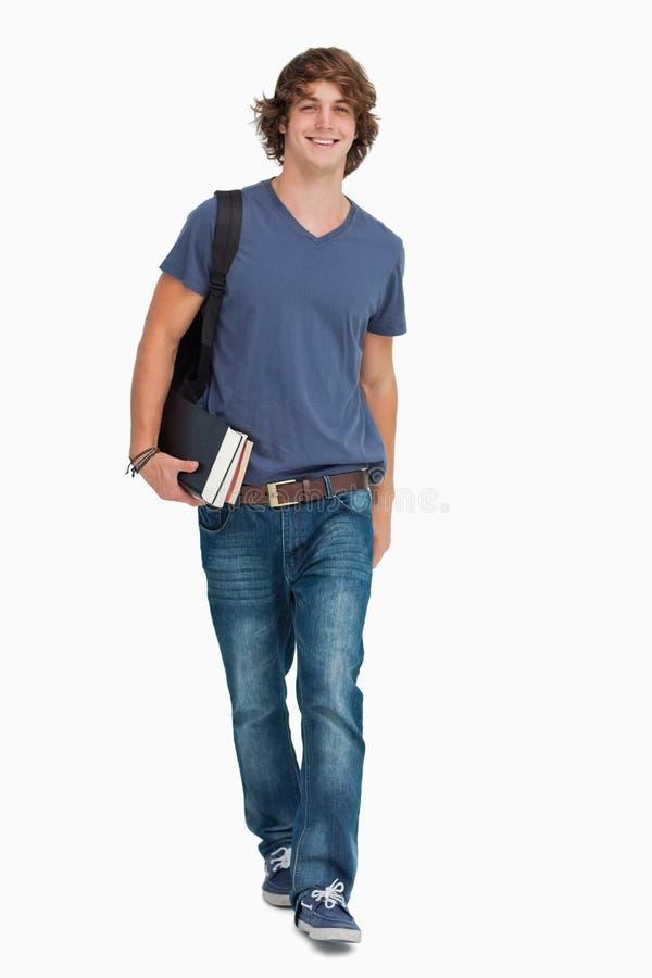 Opinião dianteira um estudante masculino que anda com uma trouxa e os livros foto de stock