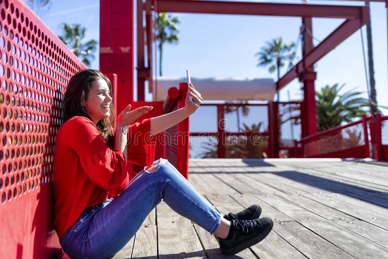 Opinião dianteira uma jovem mulher bonita de sorriso que veste a roupa urbana que senta-se na terra ao tomar um selfie e ao gesti foto de stock royalty free