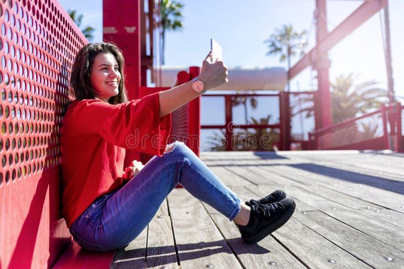 Opinião dianteira uma jovem mulher bonita de sorriso que veste a roupa urbana que senta-se na terra ao tomar um selfie e ao gesti fotografia de stock