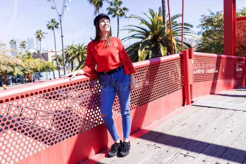 Opinião dianteira uma jovem mulher bonita que veste a roupa urbana que inclina-se em uma cerca metálica da ponte ao olhar afastad imagens de stock