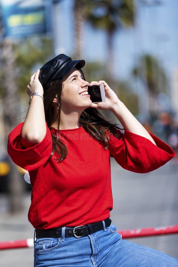 Opinião dianteira uma jovem mulher bonita que veste a roupa urbana que senta-se em uma cerca metálica ao usar um ar livre do tele fotografia de stock