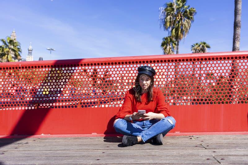 Opinião dianteira uma jovem mulher bonita que veste a roupa urbana que senta-se em um assoalho de ponte ao usar um ar livre do te fotografia de stock