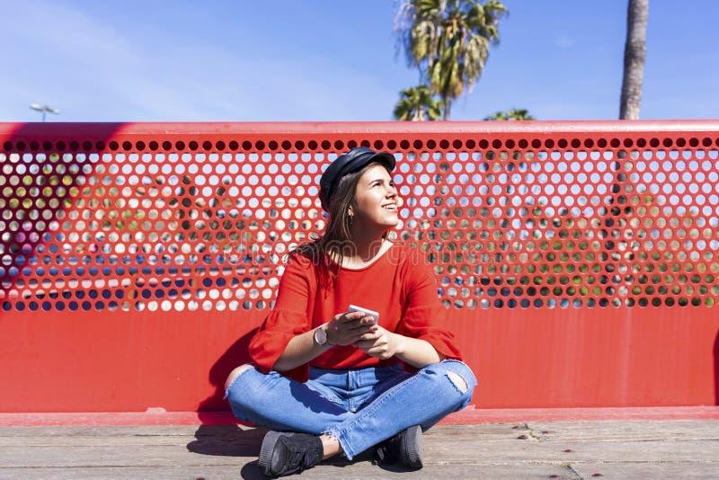Opinião dianteira uma jovem mulher bonita que veste a roupa urbana que senta-se em um assoalho de ponte ao usar um ar livre do te imagens de stock