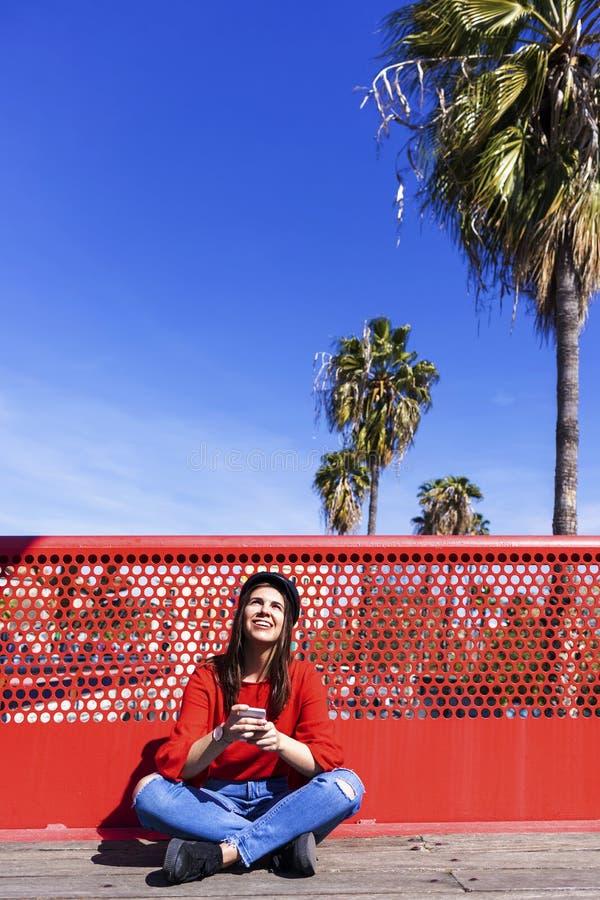 Opinião dianteira uma jovem mulher bonita que veste a roupa urbana que senta-se em um assoalho de ponte ao usar um ar livre do te foto de stock royalty free
