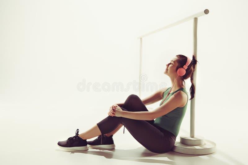 Opinião dianteira uma jovem mulher que senta-se com fones de ouvido foto de stock royalty free